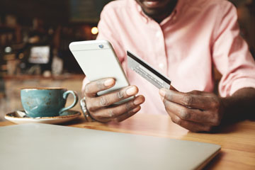 African American Man holding Credit Card and Phone